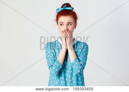 The confused young girl. girl covering mouth with both hands keeping a secret. Beautiful redhead girl in blue dress doesn't want to spread rumors or some confidential information. Isolated studio shot on gray background.