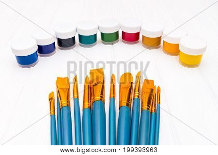 Top view of close cans of colored paint with brushes on the white wooden background
