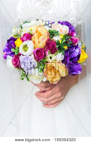 Close up wedding bouquet in bride's hands. Colorful wedding bouquet. Artificial flowers