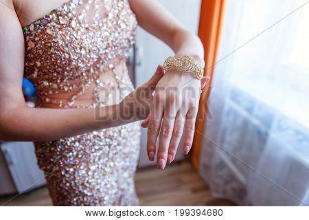 Girl in a beautiful elegant dress wearing the beautiful gold bracelet