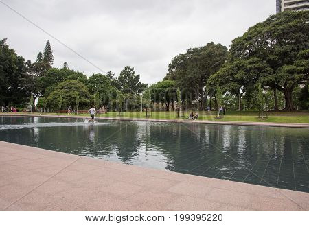 SYDNEY,NSW,AUSTRALIA-NOVEMBER 29,2016: Young adult disrespectfully running across the memorial reflection pond at Hyde Park with other tourists in Sydney, Australia.