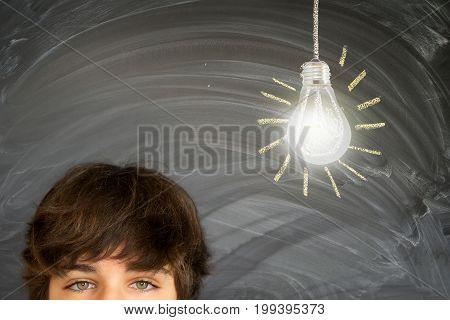 Eyes of teenager boy against getting an idea blackboard with glowing lightbulb background