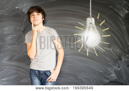 Teenager boy against getting an idea blackboard with glowing lightbulb background