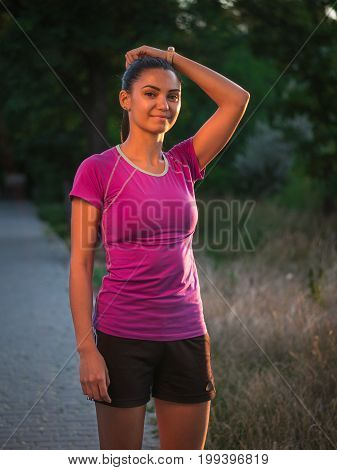 Profile portrait of happy sporty woman relaxing in park. Female model relaxing, breathing fresh air outdoors. Healthy active lifestyle concept. Copy space
