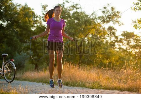 The girl is jumping rope in the park. Young girl doing sports in the forest near sea. Woman is jumping rope in the park. A young girl is doing sports in the forest