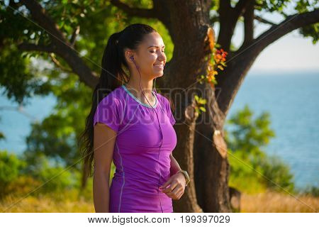 Female jogger listening music in headphones after training. Young athletic woman exercising in the park near to sea outdoors and enjoys music with earphones.