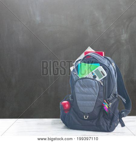 School backpack full of supplies on white desktop in classroom, copy space on blackboard