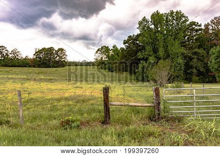 Barbed wire fence H brace and metal gate with a field in the background and storm clouds
