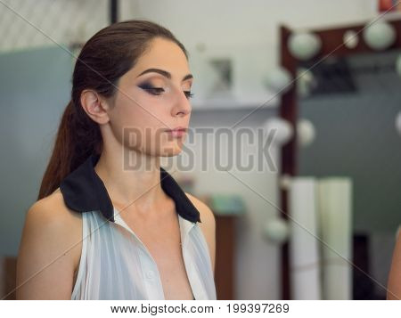 Fashion woman with red lips and smoky eyes, evening make up. Beauty. Portrait. Red background, studio shot. Perfect skin. Brunette.