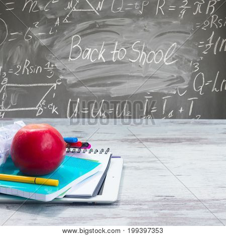 Apple with school supplies on white wooden table, blackboard with back to school letters in background