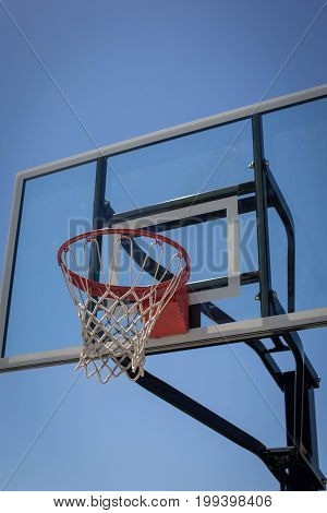 Vertical shot of a basketball hoop at a park during the day