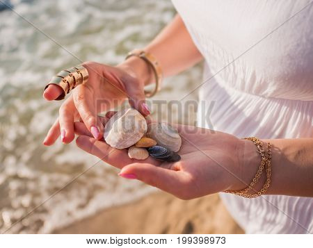 Hand holding sea shells and pumice stones found washed on rocky beach.