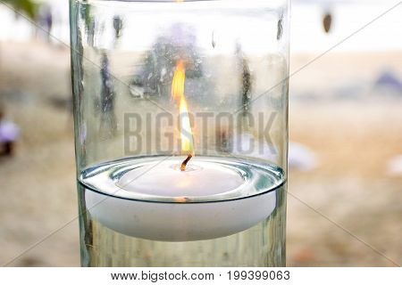 Floating candle lit in glass vase at beach