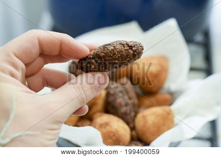Hand Holding Deep Fried Brazilian Kibbe