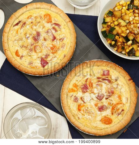 Cherry Tomato and Onion Quiches with Sauteed Corn and Summer Squash at table.