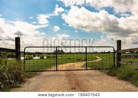 Metal gate closed on a dirt road leading into a field. Farm pond and round hay bales are visible in the background.