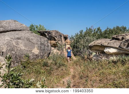 horizontal image of a caucasian woman on vacation walking among big natural sandstone rock formations on a beautiful summer afternoon.