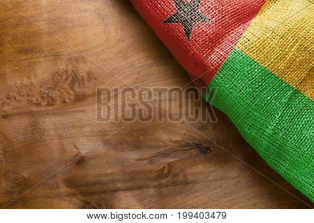 Flag of Guinea Bissau on a wooden background. Flag of canvas fabric.