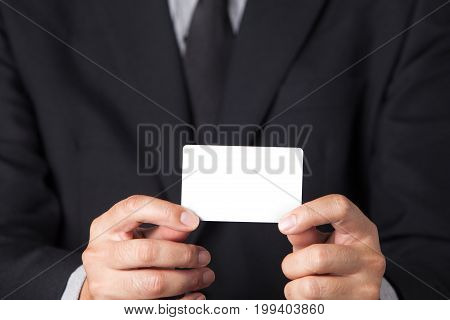 A Businessman showing his name card on his hands.