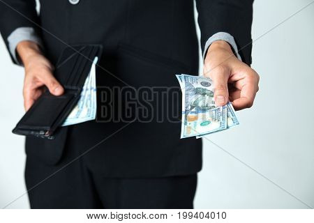 The businessman took dollar out of his wallet for pay or donation.