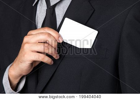 A Businessman takes a card out of his suit.