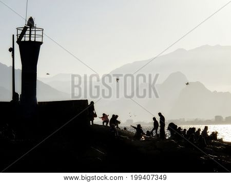 silhouetted people walking in harbor of Antalya over sunny sky