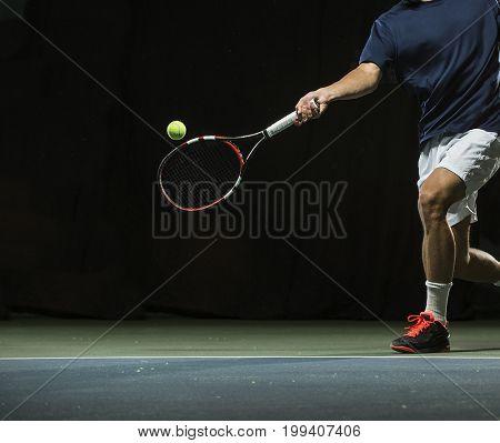 Close up photo of a man swinging a tennis racquet during a tennis match.
