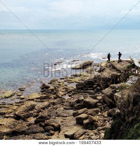 two fishermen sea fishing on rocky beach