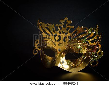 Golden mask Placed on a Black background.