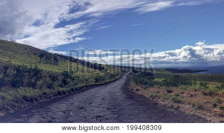 Lonely and remote rugged road, Piilani Hwy past Hana around south of Maui with Haleakala mountain, ocean and clouds in background