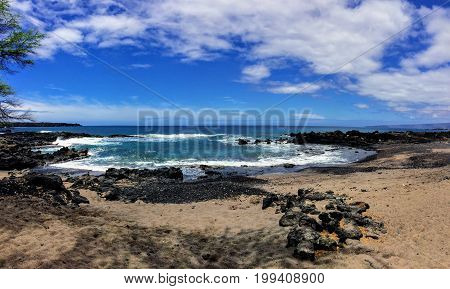 Rock and Coral with Spray of crashing waves in beach tide pools at Maluaka Beach and Kihei Maui with sky and clouds