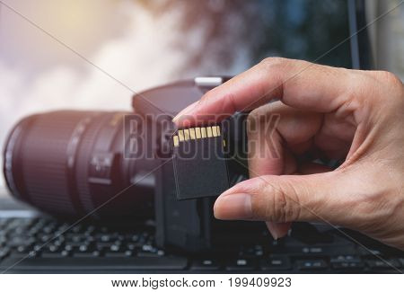 Photographer's hand holding memory card for preparing his camera before photography.