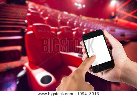 Smartphone On Hand And White Screen With Blurry Background Of Seat In Movie Theater.