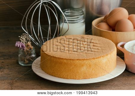 Homemade sponge cake on white plate.Soft and lite delicious sponge cake with ingredients: eggs flour milk on wood table. Homemade cake with ingredients in homemade bakery concept for bakery background. Sponge cake background concept.