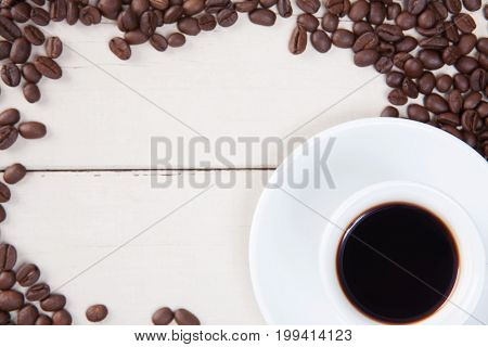 Top View Of Empty White Cup Coffee With Black Coffee And Coffee Seeds Put On White Wood Table.