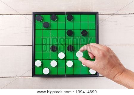 Checker Game On Green Board View From Above On Wood Table.