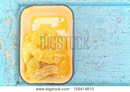 Yellow honeycombs in metallic enameled form on the old wooden background