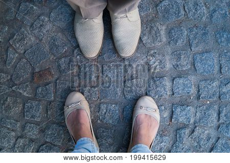 Man and woman face to face stand on cobbles. Focus on the footwear. Rendezvous concept.
