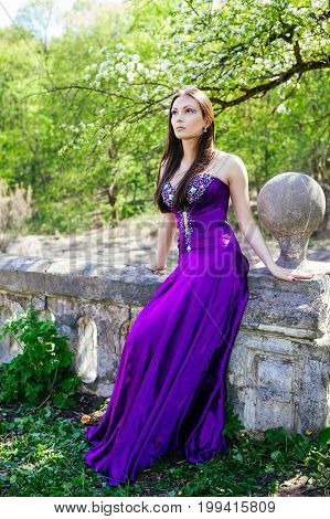 Young princess in long violet dress in the old park. Brown-haired girl acting this role.
