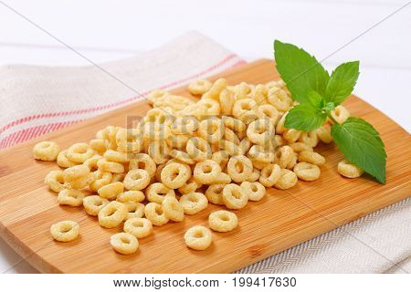 pile of honey cereal rings on wooden cutting board - close up