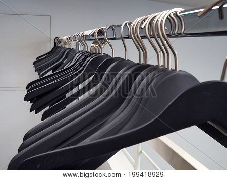 Wooden black clothes hangers on a metal rack in a wardrobe dressing room