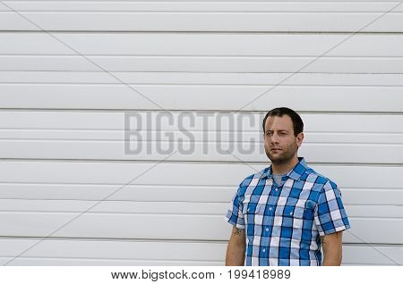 Man in a plaid shirt with a white background behind him.