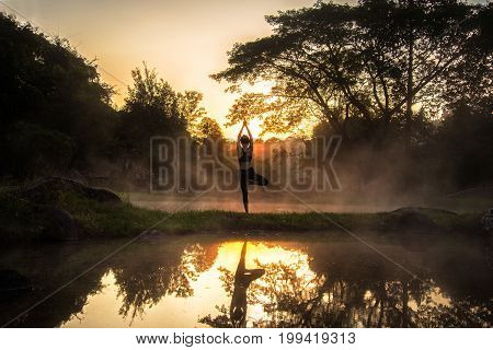 Silhouette of a beautiful Yoga healty woman in the morning at the hot spring park. Healty Concept