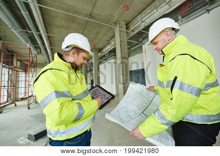 two building engineers with project at construction site