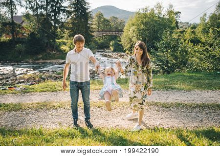 young family plaing with her daughter in mountains near river