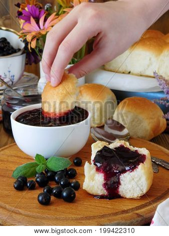 Golden buns and berry jam surrounded by berries and flowers. Female hand is dipping a bun into the jam