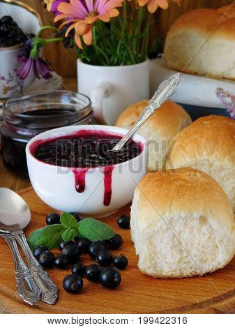 Berry jam in a ceramic bowl and golden buns surrounded by berries and flowers