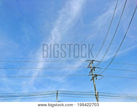 The electric poles supporting wires low voltage and high voltage on blue sky background
