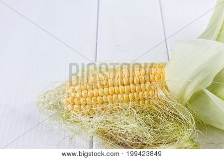 fresh corns on the wooden white background