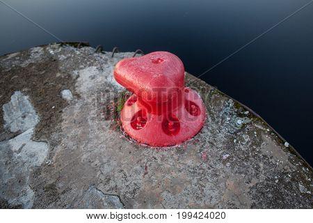 Old red steel bollard on a pier